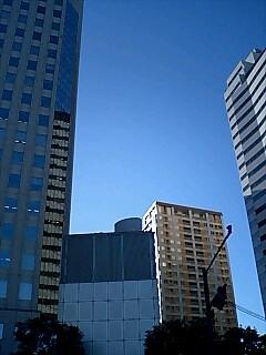青い空、グレーのビル、黒いスーツの僕